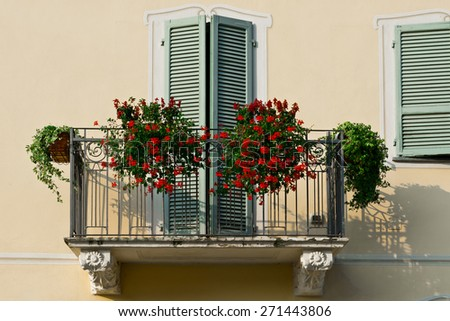 The Renovated Facade of the Old Italian House with Balcony Decorated with Fresh Flowers  - stock photo