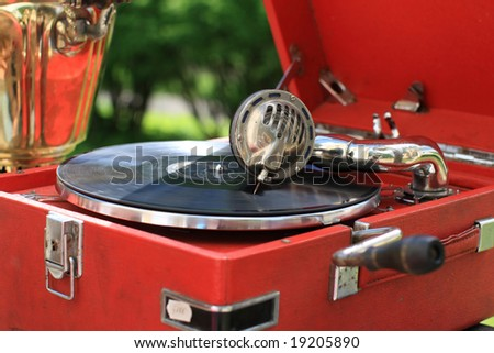 The retro portable gramophone with disc, outdoor - stock photo