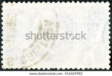 The reverse side of a postage stamp on a black background - stock photo