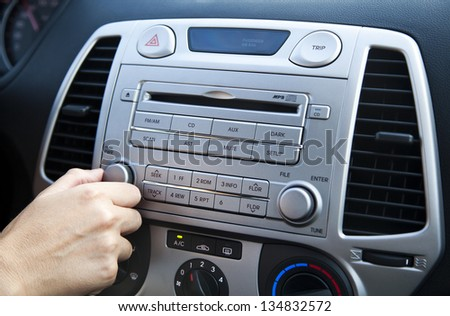 The right hand of an adult woman adjusting the sound volume in the car stereo - stock photo