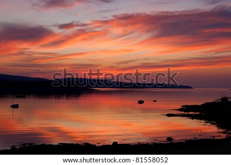 The rising sun bathes a harbor in Acadia National Park in red light. - stock photo