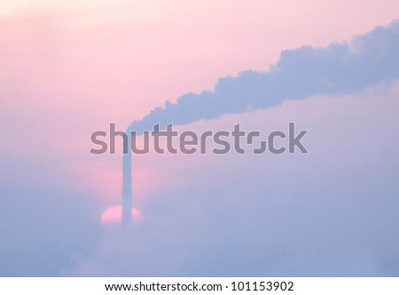 The rising sun over a steaming pipe. Frost and fog. - stock photo
