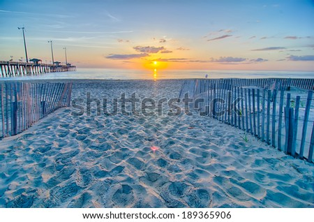 The rising sun peeks through clouds and is reflected in waves by the Nags Head fishing pier on the outer banks of North Carolina - stock photo