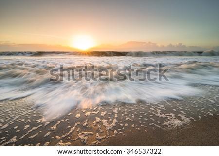 The rising tide rushing in towards land on Edisto Island, South Carolina during the sunrise. - stock photo