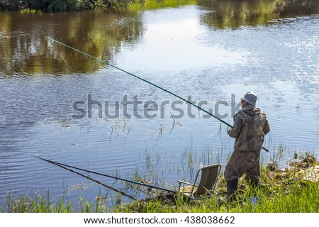 The river Kargat, Novosibirsk oblast, Siberia, Russia - June 12, 2016: a fisherman catches a fish on the river on a float