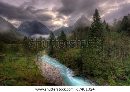 The river through the Alpine valley with dramatic sky. The Soca river, Slovenia - stock photo