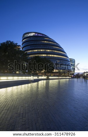 The Riverside area on the Thames and London city hall at night. - stock photo