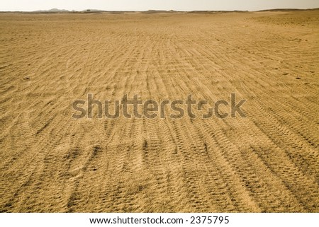 the road in a desert with tracks from cars - stock photo