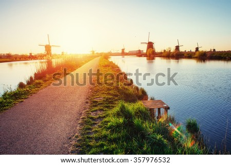 The road leading to the Dutch windmills from the canal in Rotterdam. Holland. Netherlands  - stock photo