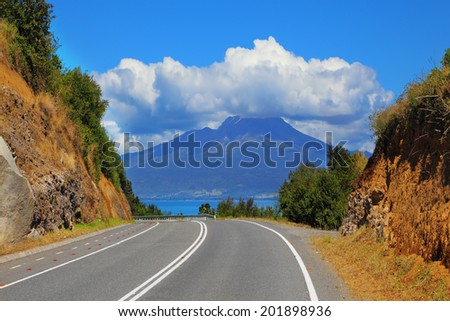 The road leads to the famous volcano Osorno. Top of the volcano cloud closed. Scenic highway in South America - Carretera Austral
