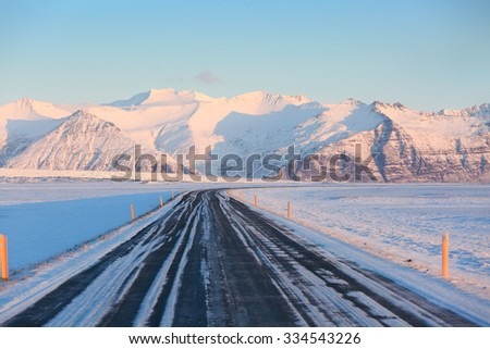 The road on a sunny day to the snow-capped mountains. The Ring Road (Route 1) of Iceland, between Hof and Jokulsarlon. South of Iceland - stock photo