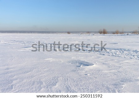 The road on snow cover of the frozen river in the winter