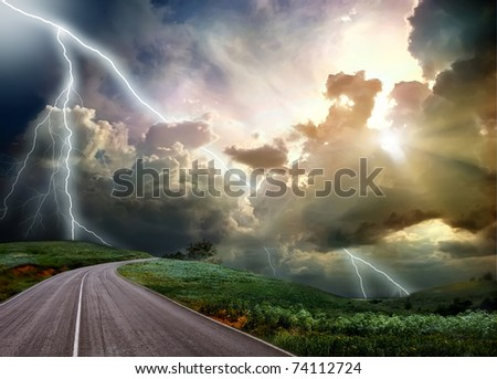 The road through the meadow and the stormy skies - stock photo