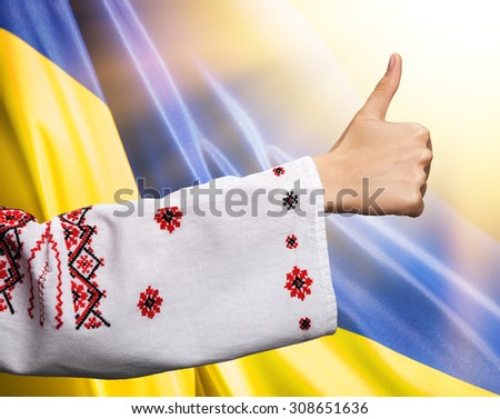 The road to freedom and light. Patriot concept. Young woman hand in the Ukrainian national clothes shows symbol ok with thumbs up against Ukrainian flag background with sun light