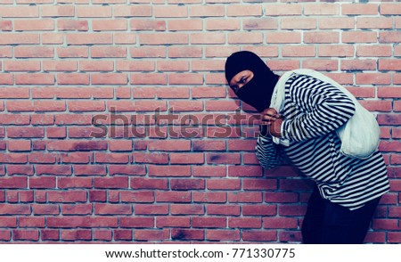 The Robber Or Thief Robbed Bank And Is Carrying Bag Of Money On Vintage Brick  Wall