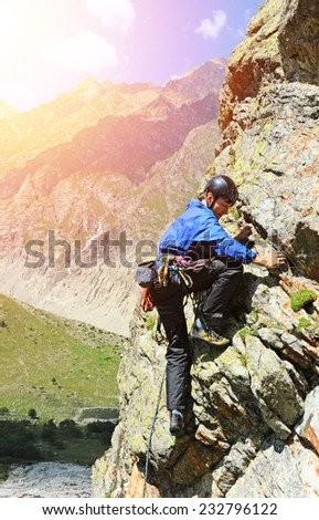 The rock-climber during rock conquest - stock photo