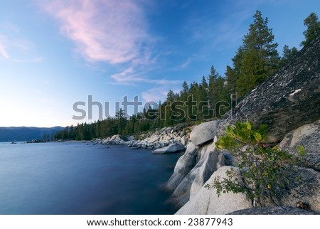 The rocky and heavily forested coastline of Lake Tahoe at sunset - stock photo
