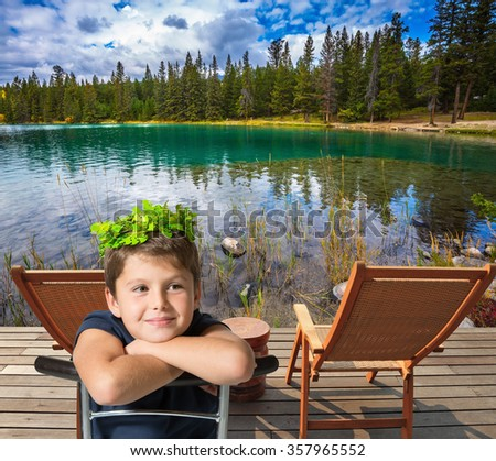 The Rocky Mountains of Canada. Two convenient chaise lounges on the bank of round lake. The beautiful boy in a carnival wreath - stock photo