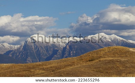 The Rocky Mountains of Montana Mission Mountain Range between Missoula and Kalispel with snow capped peaks, blue sky with clouds, and prairie grass lands, on the Flathead Indian Reservation