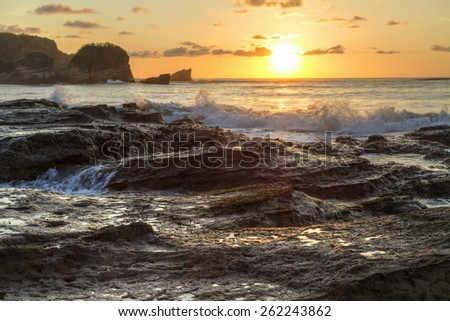 The rocky shore and headland silhouetted at Playa Pelada with the surf crashing at sunset on the Pacific coast of Costa Rica. - stock photo