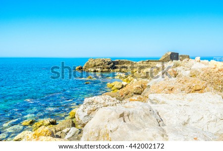 The rocky shore of Caesarea with the ancient building ruins on the background, Israel.