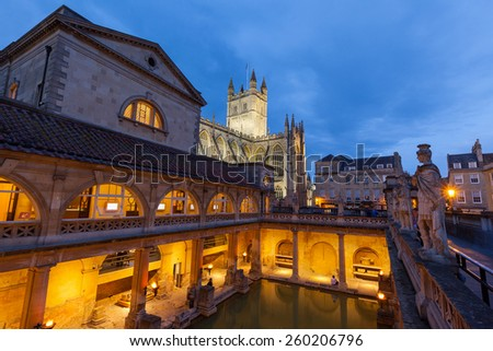 The Roman Baths and Bath Abbey at night in Bath, England. The Baths and Abbey are popular tourist attractions in the centre of the historic British city. - stock photo
