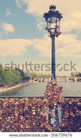 The romantically love inscribed padlocks on the Pont Des Arts Bridge, Paris France. with retro vintage Instagram style effect. - stock photo