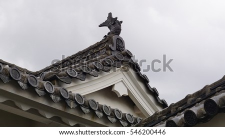 The roof of the Japanese Castle with antique fish stucco on top in black and white color, the unique of texture pattern design of gable with there family stamp logo sign