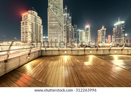 The roof platform and the modern urban context at night - stock photo