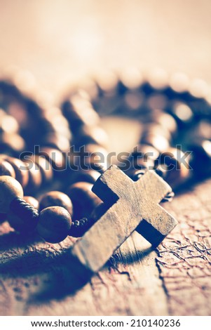 the rosary on old wooden table - stock photo