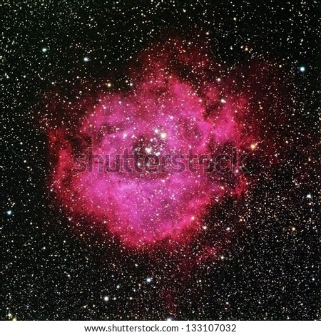 The Rosette Nebula is a large cloud of glowing gas approximately 130 light years accross surrounding a cluster of young stars in the constellation Monoceros - stock photo