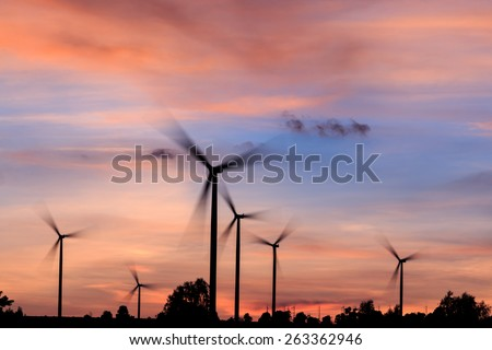 The rotation of the wind turbines silhouette at sunset - stock photo