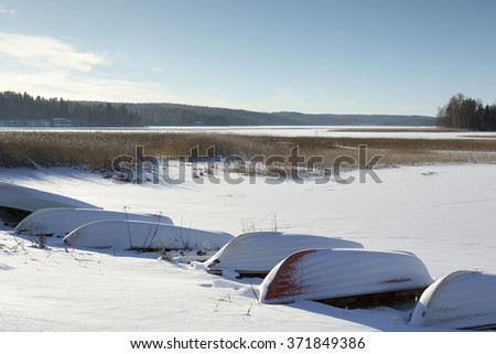 The rowing boats are parked on the shore for winter season. Some snow are on the boats and on the ground. Image taken during sunny spring day in Finland. - stock photo