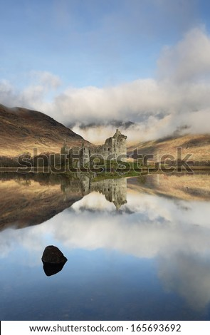 The ruin of Kilchurn Castle and mountains reflecting off Loch Awe, Scotland. - stock photo