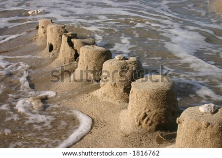The ruins of a sand castle being swept away by the sea - stock photo
