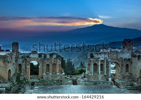 The ruins of the  amphitheater on background Etna at sunset - stock photo