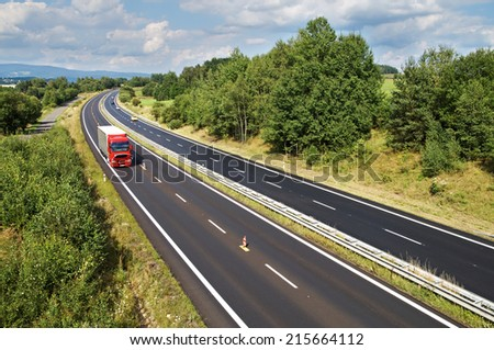 The rural landscape with a highway lined with trees, red truck and cars on the road, view from above - stock photo