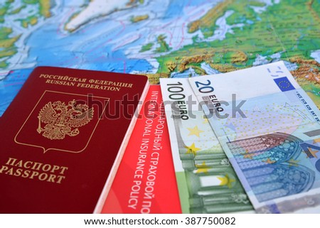 The Russian international passport, euro and the international insurance policy lie on a map