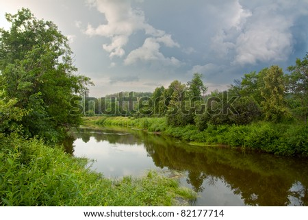 The Russian river among trees with huge clouds and reflection in water - stock photo