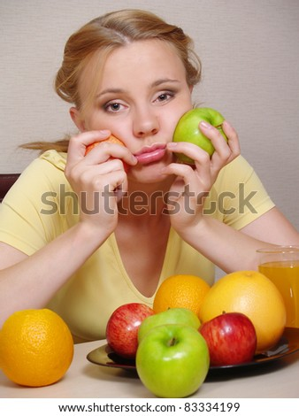 The sad beautiful girl with fruit sits at a table