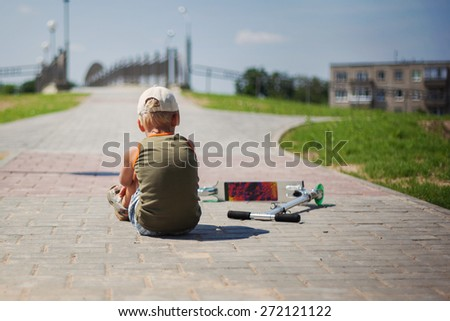 The sad  boy sits a back, fell from the scooter in open air - stock photo