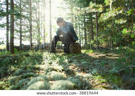 The sad young man sits in wood on a stone - stock photo
