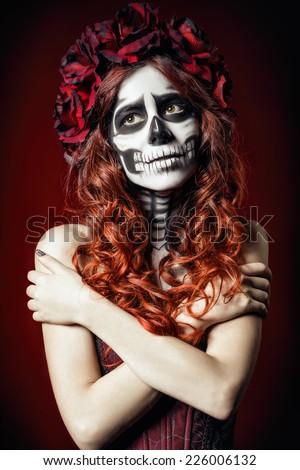 The sad young woman with muertos makeup (sugar skull) - stock photo