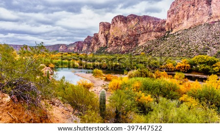 The Salt River and surrounding Mountains in the state of Arizona with fall colored shrubs and trees - stock photo
