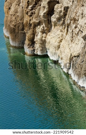 The salty shore of the Dead Sea on the Jordan side, with salt formations. The markings on the rock face indicate that the waters are receding. - stock photo