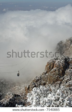 The Sandia Mountain tram rises out of the clouds of an early winter storm - vertical orientation - stock photo