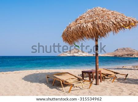 The sandy beach near the blue sea with sun beds and umbrellas. Mykonos - stock photo
