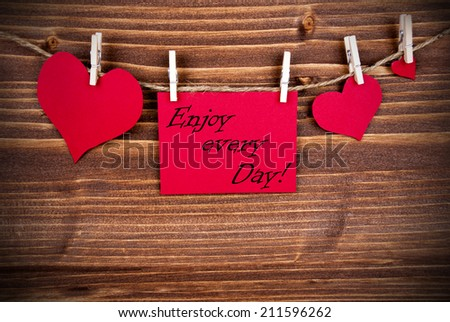 The Saying Enjoy every Day on a red Label with Hearts Hanging on a Line on a Wooden Background - stock photo