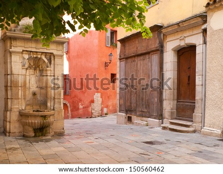 The scenic streets of Grasse with the old fountain and red house, France. - stock photo