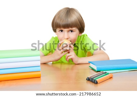the schoolboy at the Desk bites from Apple - stock photo